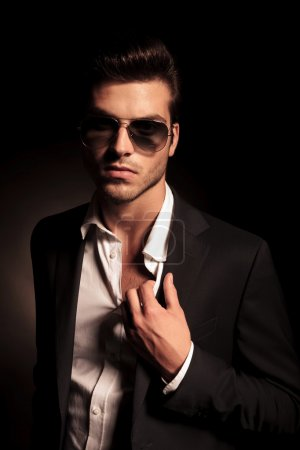 man in suit and sunglasses holding his suit by collar