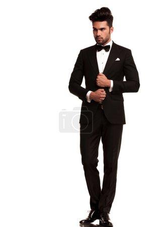 Photo pour Image pleine longueur d'un élégant jeune homme de mode ajustant son smoking tout en regardant de son côté, loin de l'appareil photo. sur fond blanc - image libre de droit