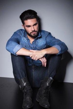 Photo pour Beau homme en chemise bleue assis et pensant - image libre de droit