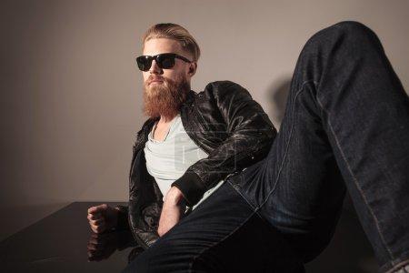 Photo pour Angle de vue d'un modèle masculin en veste de cuir et lunettes de soleil assis sur le sol, à la recherche de suite - image libre de droit