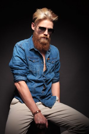 Fashion man in blue shirt and sunglasses sitting