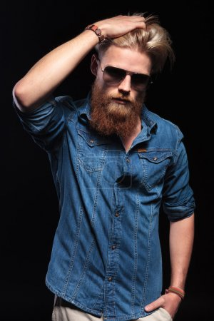 man with red beard and sunglasses fixing his hair.