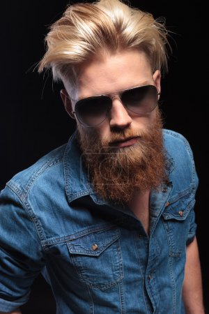 man with red beard wearing sunglasses, posing for the camera
