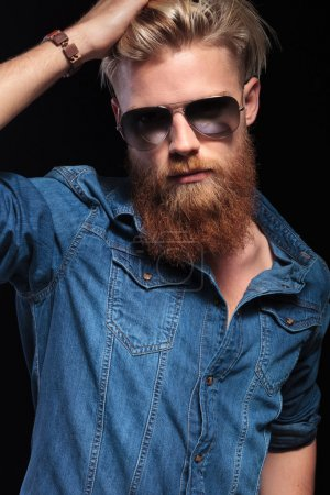 man with long red beard wearing sunglasses, fixing his hair