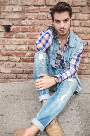 Photo for Picture of a cool young man sitting on the sidewalk with one hand on his neck and the other one on his leg, looking at the camera - Royalty Free Image