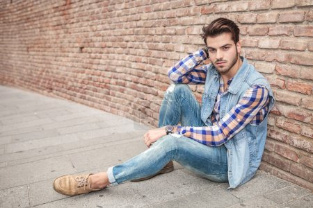 Photo for Side view of a handsome man resting on the sidewalk, leaning against a brick wall with one hand at his neck, looking at the camera - Royalty Free Image