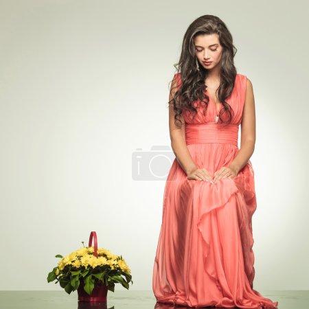 Elegant woman  sits near flower basket and looks down