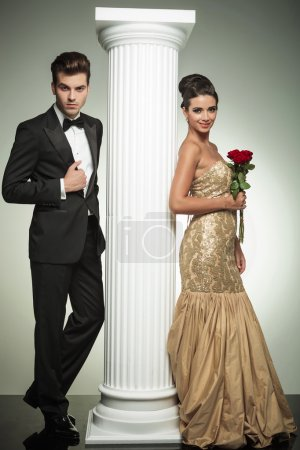 full body picture of an elegant couple near column