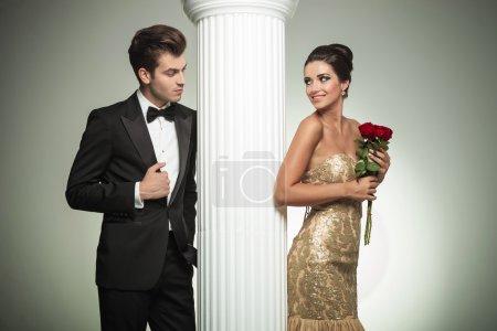 Photo pour Jeune couple élégant se regardant près de la colonne, photo de studio - image libre de droit