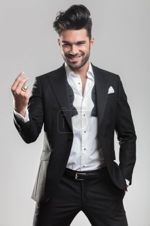 Elegant young man in tuxedo snapping his finger