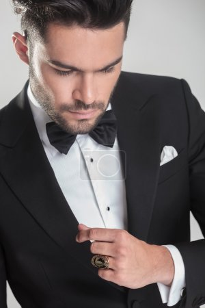 elegant young man in tuxedo looking down