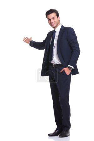 Photo pour Vue latérale d'un homme d'affaires heureux vous accueillant d'une main dans sa poche tout en souriant, sur fond blanc - image libre de droit