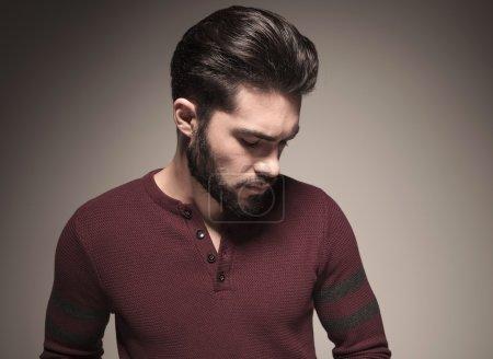 man wearing a burgundy sweater, looking down