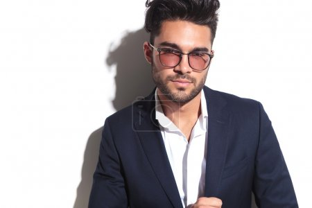 Young business man wearing sunglasses looking at the camera