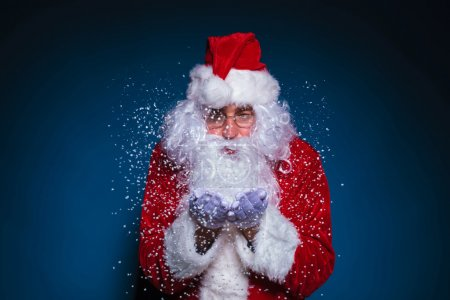 Photo for Santa Claus with glasses blowing snow on blue background - Royalty Free Image