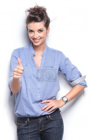 Foto de Happy casual fashion woman showing the thumbs up gesture while posing for the camera. - Imagen libre de derechos
