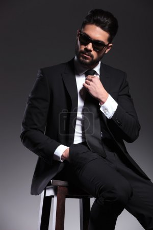 Handsome young elegant business man sitting on a stool