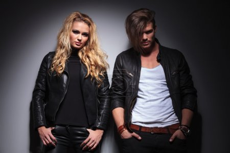 Young fashion couple leaning on a grey wall