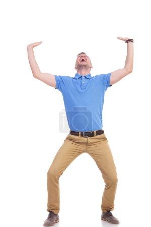 Photo pour Image pleine longueur d'un jeune homme décontracté tenant quelque chose d'imaginaire au-dessus de lui avec les deux mains et criant hors de difficulté. homme occasionnel écrasé. isolé sur un fond blanc - image libre de droit