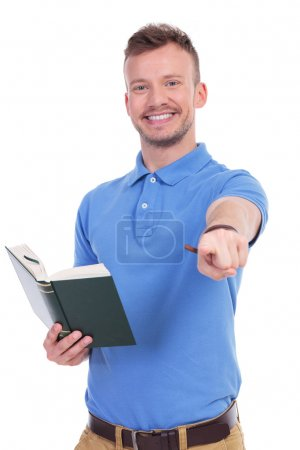 young casual man with book points at you