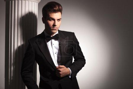 Photo pour Jeune homme d'affaires élégant posant près de colonne blanche tout en fixant sa veste . - image libre de droit