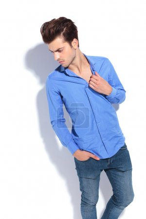 fashion man looking down while pulling his blue shirt.