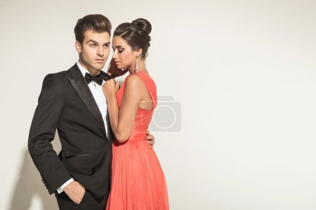 Photo pour Photo d'un jeune couple élégant posant, l'homme regarde loin avec une main dans sa poche, tandis que sa femme si l'embrasser . - image libre de droit