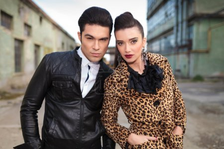 Young fashion couple posing, both holding hands in pockets.