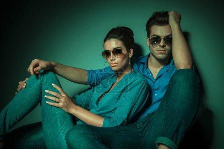 fashion couple sitting on studio background