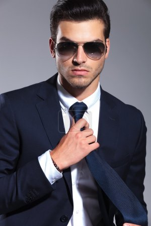 business man pulling and fixing his tie