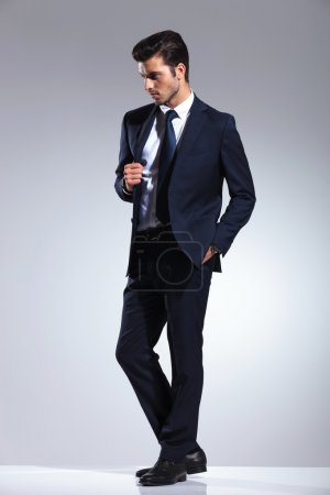 Photo for Side view picture of a elegant business man holding one hand in his pocket while pulling his jacket. - Royalty Free Image