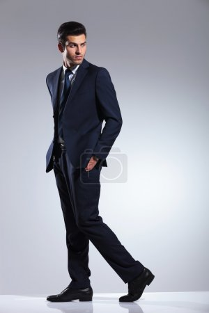 Photo for Side view picture of a young business man walking on grey studio background with his hands in pockets. - Royalty Free Image