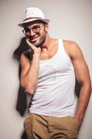 Happy young casual man leaning on a white wall