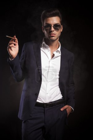 young handsome business man enjoying a cigarette