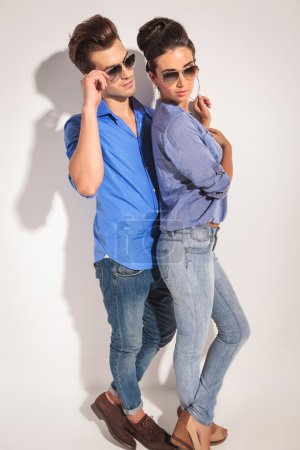 Side view of a casual couple posing near a  wall