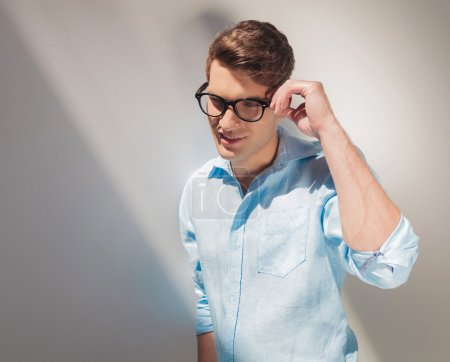 Smiling young casual man fixing his glasses