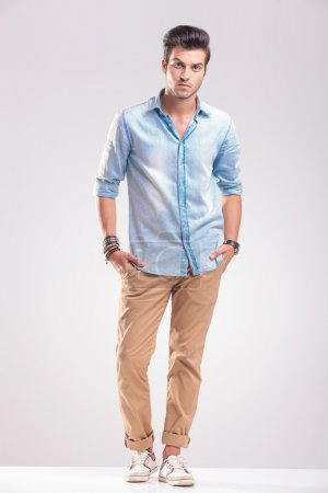 Photo for Handsome casual young man standing with his hands in pockets, on grey studio background. - Royalty Free Image