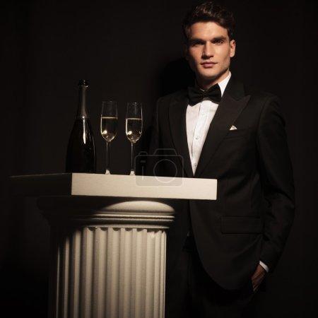 elegant business man standing near a white column