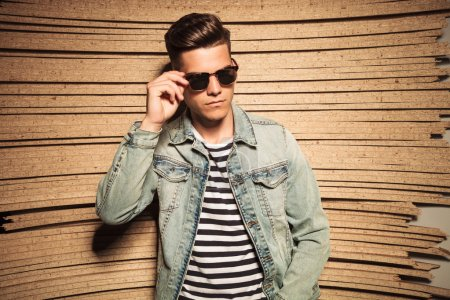 cool young casual man taking off his sunglasses