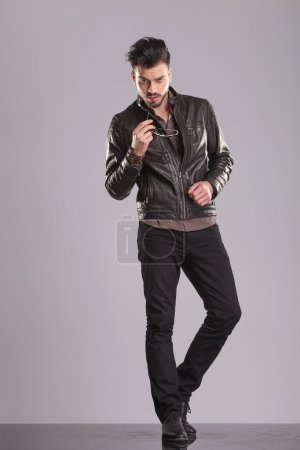 Photo for Full body picture of a young handsome man standing on studio background, touching his lips with a pair of sunglasses. - Royalty Free Image