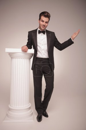 Photo pour Image pleine longueur d'un bel homme d'affaires élégant tenant sa main sur une colonne blanche tout en vous accueillant . - image libre de droit
