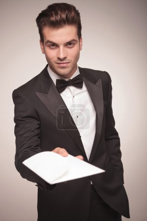 Attractive young business man offering you a invitation.