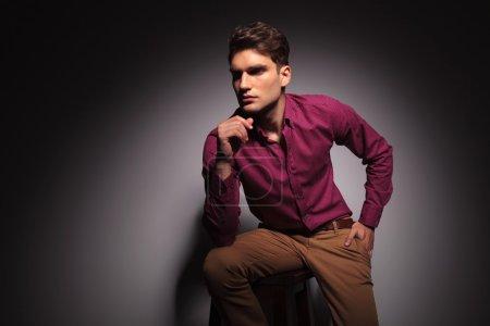Photo pour Vue latérale d'un jeune homme beau assis sur un tabouret avec une main dans sa poche . - image libre de droit