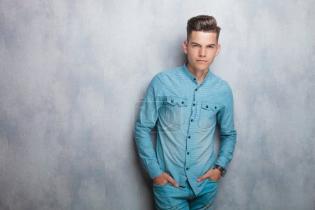 Casual young man leaning on a grey wall.