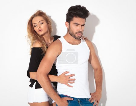 Side view of a young casual couple posing