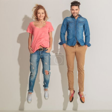 Young casual couple jumping