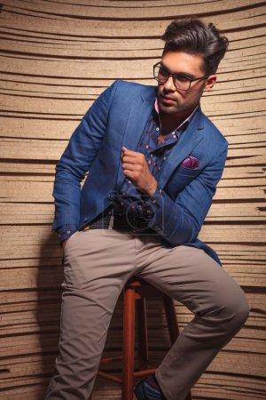Photo pour Homme de mode attrayant assis sur une chaise tout en regardant loin . - image libre de droit