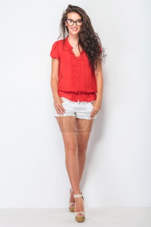 beautiful young woman standing with her legs crossed.
