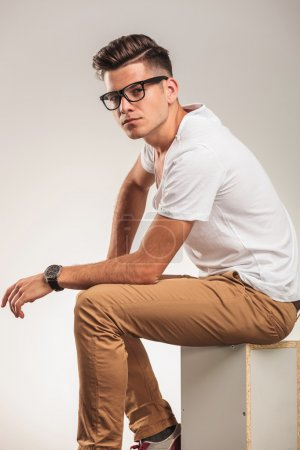 Photo for Young man sitting on a chair and looking smart wearing glasses - Royalty Free Image