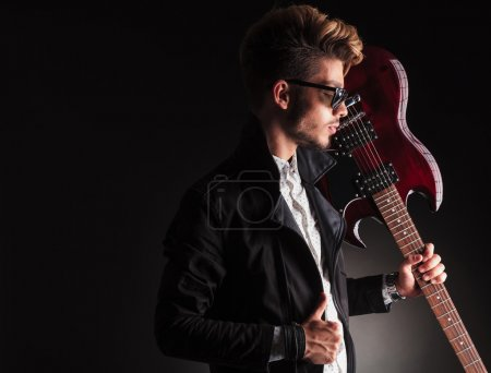 cool young guitarist holding his electric guitar on shoulder